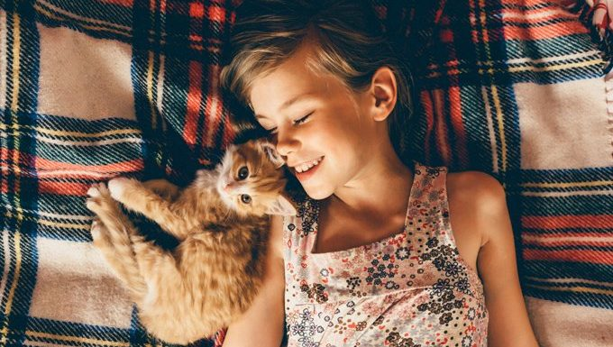 girl lying with cat on blanket