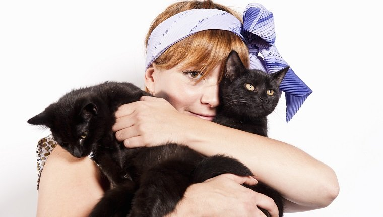 Woman embracing her cats