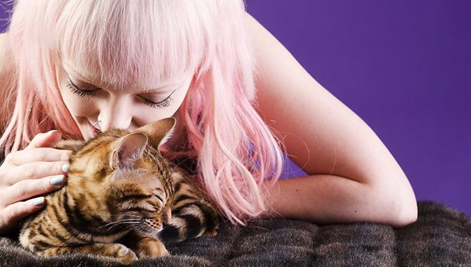 woman with pink hair massaging cat