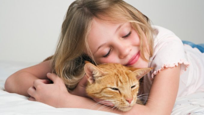girl hugging cat