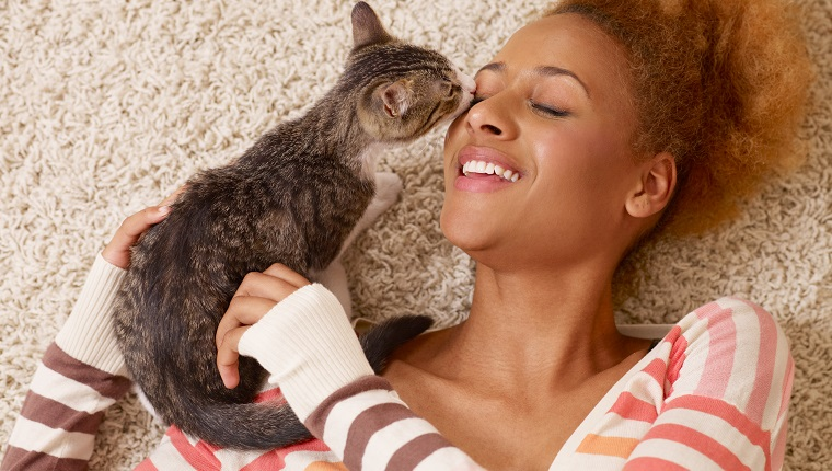 """portrait of attractive young african woman with curly hair laying in carpet, while playing with little cat"""